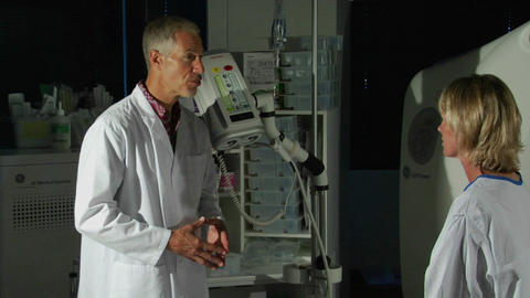 A man in a lab coat explains medical equipment to a patient Stock Video Footage
