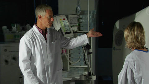 A man in a lab coat explains medical equipment to a patient Footage