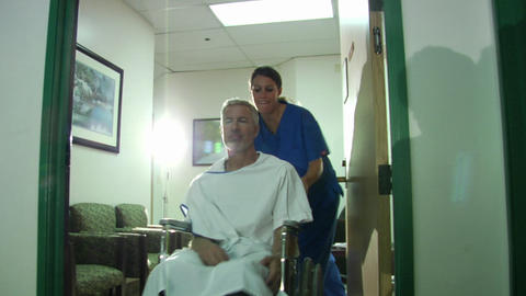 A nurse pushes a patient in a wheelchair Stock Video Footage