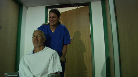 A nurse pushes a patient in a wheelchair Footage