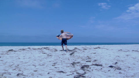 A boy runs with a skimboard on a beach Stock Video Footage