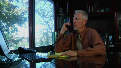 A business man speaks on a phone and works at a computer Stock Video Footage
