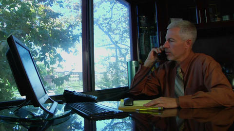 A business man speaks on a phone and works at a computer Footage