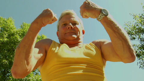 An Older Man Flexes His Muscles stock footage