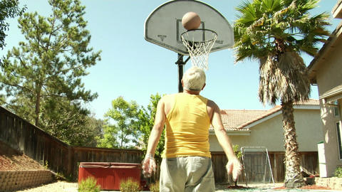 An older man dribbles and shoots a basketball Footage