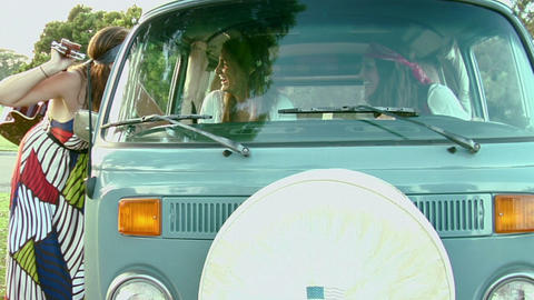 A woman passes a guitar into a VW Bus Stock Video Footage