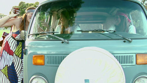 A woman passes a guitar into a VW Bus Footage