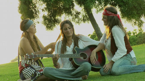 A woman plays a guitar while two others play with her hair Stock Video Footage