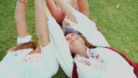 Women lie on the grass and give peace signs Footage