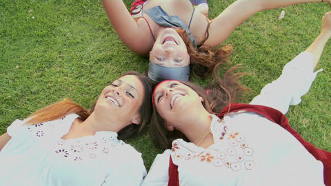 Women lie on the grass and give peace signs Stock Video Footage