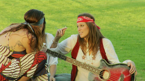 Women dressed like hippies sit in the grass and smoke Stock Video Footage