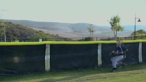 A young baseball player catches a ball as it almost goes... Stock Video Footage