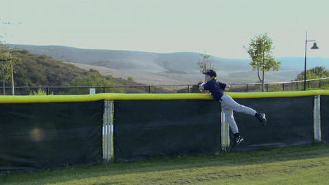 A young baseball player catches a ball as it almost goes over the back fence Footage