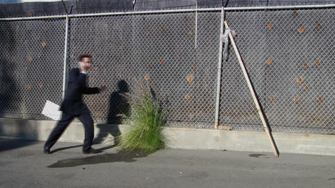 A young man wearing a business suit runs from water balloons Stock Video Footage