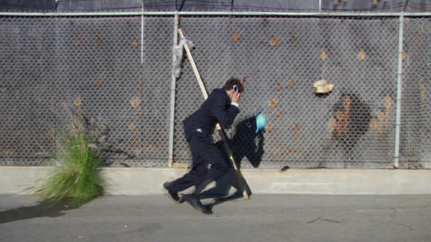 A young man wearing a business suit runs from water balloons Footage