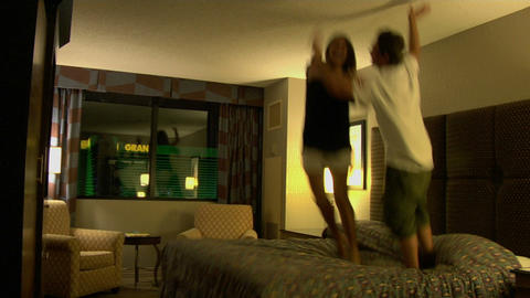 A young woman and man jump on a hotel room bed Stock Video Footage