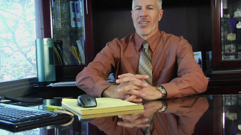 A businessman leans forward on his desk and clasps his... Stock Video Footage