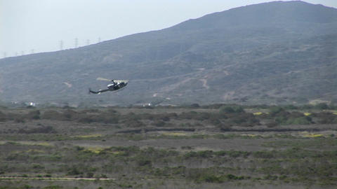 A helicopter lands on an Oceanside landing strip Stock Video Footage
