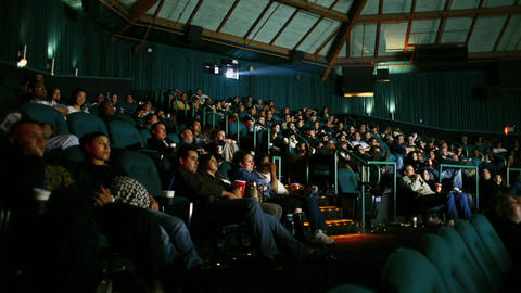 An audience watches a film in a darkened movie theater Footage