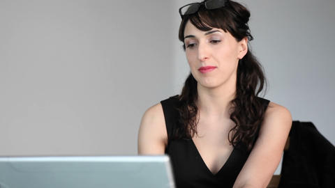 A woman focuses her attention between her laptop and talking to someone in the room Footage
