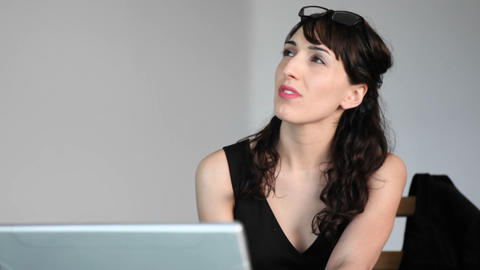 A woman focuses her attention between her laptop and... Stock Video Footage