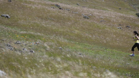 A young woman runs up a hillside Stock Video Footage