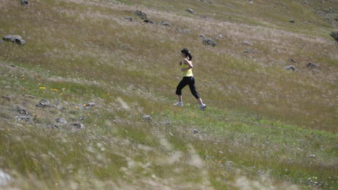 A young woman runs up a hillside Footage