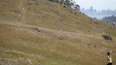 A woman jogs up a hill Stock Video Footage