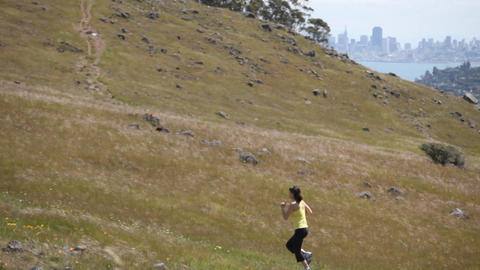 A woman jogs up a hill Footage
