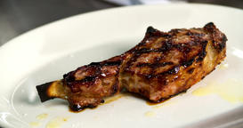 Serving grilled barbecue meat bone steak 4k video. Fried beef on plate spice Footage