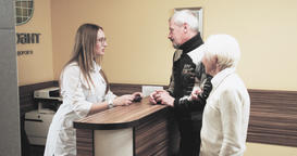 Old patients talking nurse hospital reception desk 4k video. Couple visit clinic Footage