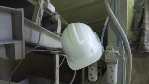 White safety helmet hanging on steel constructions on manufacturing site Live Action