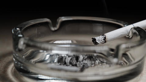 A smoldering cigarette on the edge of a typical glass ashtray. Stop smoking Live Action