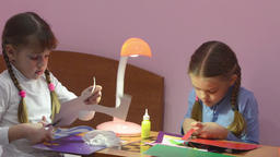 Two children cut with scissors pieces of colored paper, making crafts Footage