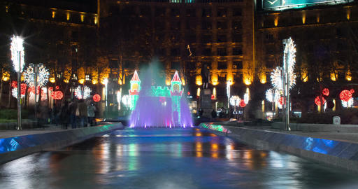 Fountain at night. People passing. Nicely lit building. Christmas decorations