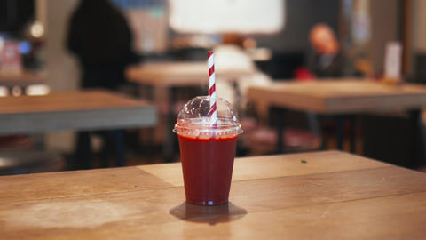 Red smoothie with a red and white striped straw on a wooden restaurant table Live Action