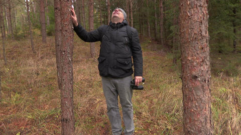 Man staring at the tree tops with binoculars Footage