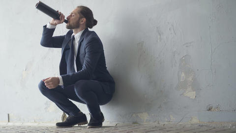 Alcoholic businessman sitting in underground crossing and drinking alcohol from Live Action