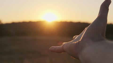 Male Hand against Sunset. Touch the Sun. Sun Shines through fingers. Slow motion Live Action