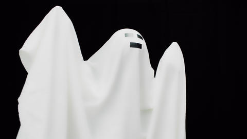 White cast in sheet on black background. Ghost in white sheet. Halloween mood Live Action