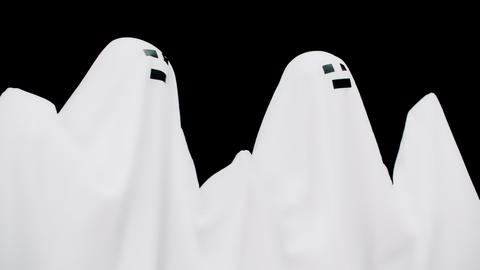 Couple white cast in sheet on black background. Two ghost in white sheet Live Action