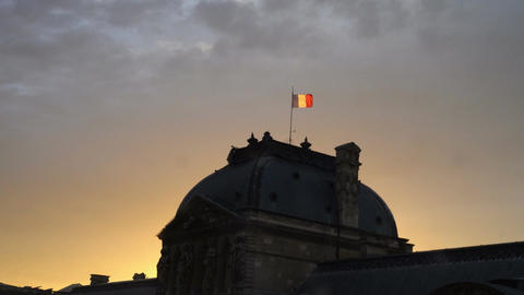 Flag of France at the top of Sully wing of Louvre Museum at dusk Live Action