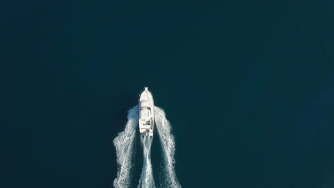 Aerial - Top down tracking shot of a bigger speed boat cruising on water Footage