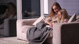 Mom teaching daughter to read at home Footage