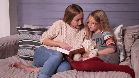 Mother and daughter reading story at home together Footage