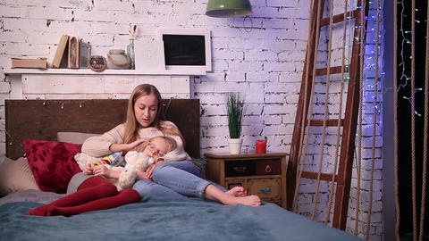 Young woman caressing her daughter to fall asleep Footage