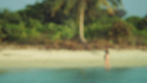 Girl walking barefoot on the water along deserted beach. Woman walking on a trop Footage
