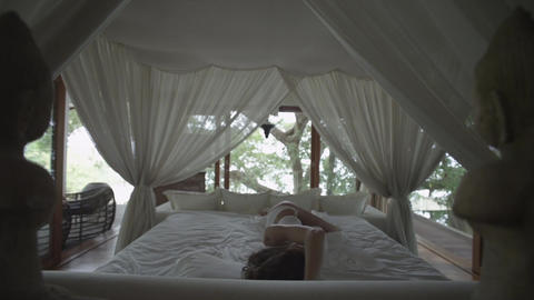 Sleeping girl wakes up. Romantic bed under the canopy. Bedroom in the forest. Wo Footage