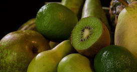Still life green fruits rotation 4k looped video copy space. Black background Footage