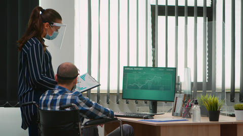 Woman with mask pointing on desktop talking with disabled colleague Live Action